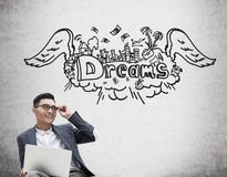 Asian businessman with laptop dreaming about holiday Royalty Free Stock Images