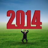 Asian businessman lifting a New year 2014 Stock Photo