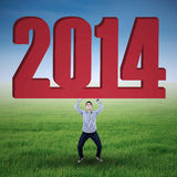 Asian businessman lifting new year 2014 Royalty Free Stock Image