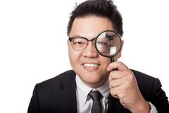Asian businessman look through magnifying glass and smile Royalty Free Stock Photo