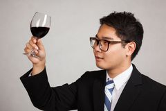 Asian businessman look at red wine stock photo