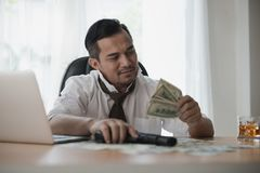 Asian Businessman looking money. And holding a gun at office desk Stock Image