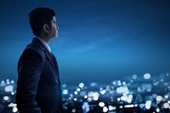 Asian businessman looking at night city royalty free stock image