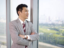 Asian businessman. Looking out of window in office Royalty Free Stock Image