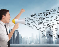 Asian businessman with megaphone shouting TAX announcement. With modern building background Stock Images