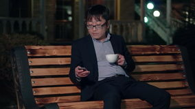 Asian businessman in the night park uses a smartphone and drinking a cup of coffee. Smiling stock footage