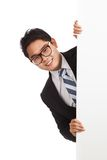 Asian businessman peeking from behind blank banner Royalty Free Stock Image