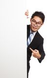 Asian businessman peeking from behind blank banner and point Royalty Free Stock Photography