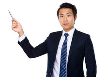Asian businessman with pen pointing up Stock Photo
