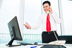 Asian businessman on phone working in office Stock Photography