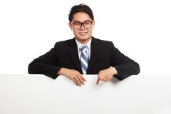 Asian businessman point down behind blank banner Stock Photo