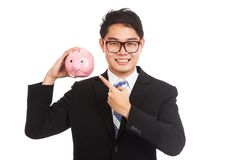 Asian businessman point to a pink piggy bank Stock Photo