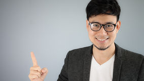 Asian businessman pointing. Asian businessman in black suit royalty free stock images
