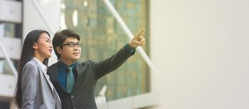 Asian businessman pointing at something. And looking in to the sky Stock Image