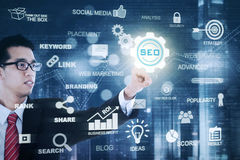 Asian businessman presses SEO icon Stock Photography