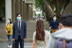 Asian businessman in protective mask. Portrait of middle-aged Asian businessman wearing facial mask in order to protect himself from smog while crossing road Stock Photos
