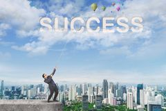 Asian businessman pulling success word in the sky royalty free stock images