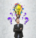 Asian businessman, purple questions and bulb. Portrait of a smiling Asian businessman standing near a concrete wall and looking at purple question marks Stock Photos