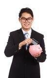 Asian businessman put credit card to piggy bank Royalty Free Stock Photos