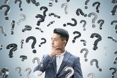 Asian businessman, question marks falling Royalty Free Stock Image