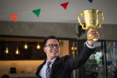 Asian businessman raising up hand and holding a golden trophy cup to cheerful and celebrated his successful in career and mission. Concept of winner and stock photos