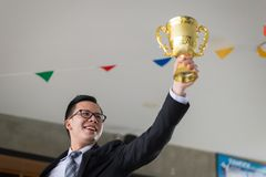 Asian businessman raising up hand and holding a golden trophy cup to cheerful and celebrated his successful in mission. Asian businessman raising up hand and royalty free stock images