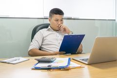 Asian businessman reading and checking report at office stock photos