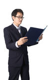 Asian businessman reading important information in file folder, Stock Photography