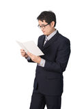 Asian businessman reading notebook or diary for checking, isolat. Ed on white background Stock Images