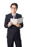 Asian businessman reading notebook or diary for checking, isolat. Ed on white background Stock Image