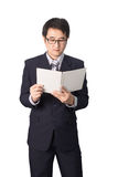 Asian businessman reading notebook or diary for checking, isolat. Ed on white background Royalty Free Stock Photography