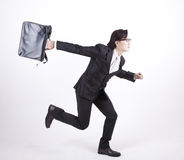 Asian businessman running isolated on white. Young Asian businessman running carrying a laptop bag Royalty Free Stock Photos