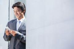 Asian businessman sending text message Stock Photos