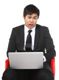 Asian businessman shocked surprise by laptop computer Stock Image