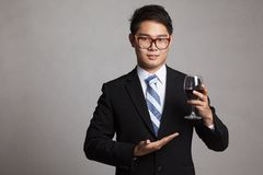 Asian businessman show a glass of red wine stock image