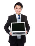 Asian businessman show with laptop computer. Isolated on white background Royalty Free Stock Photography