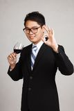 Asian businessman show OK with glass of red wine Royalty Free Stock Photography