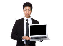 Asian Businessman showing the blank screen of laptop computer. Isolated on white background stock image
