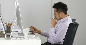 Asian businessman sit in front of computers. Young Asian businessman sitting in front of computers and thinking in serious manner in modern office. Concept for stock video footage