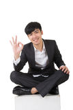 Asian businessman sit and give you an okay sign Royalty Free Stock Image