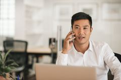 Asian businessman sitting at his desk talking on a cellphone. Young Asian businessman working on a laptop and talking on a cellphone while sitting at a desk in a Royalty Free Stock Photos