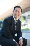 Asian businessman sitting outdoors Royalty Free Stock Photos
