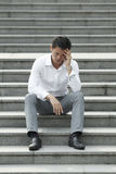 Asian businessman sitting steps holding his head Royalty Free Stock Photography