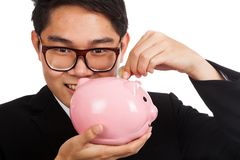 Asian businessman  smile put a coin to a pink piggy bank Royalty Free Stock Photos