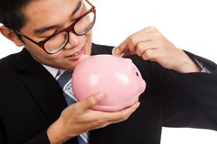 Asian businessman  smile put a coin to a pink piggy bank Stock Images