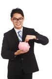 Asian businessman  smile put a coin to a pink piggy bank Royalty Free Stock Photography