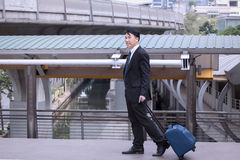 Asian Businessman smiling and happy, wearing suit with luggage,. Walking on business street for travelling on vacation tourist business trip concept Royalty Free Stock Photography