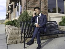 Asian Businessman smiling and talking on the mobile phone on the bench. Asian Businessman smiling and talking on the mobile phone and having coffee on the bench Stock Photo