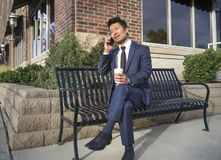 Asian Businessman smiling and talking on the mobile phone on the bench. Asian Businessman smiling and talking on the mobile phone and having coffee on the bench Stock Photos