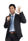 Asian businessman speaking with microphone show OK sign Royalty Free Stock Images